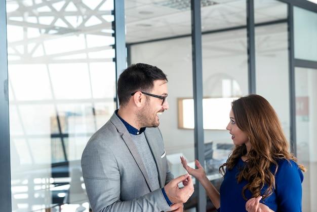 Dwóch biznesmenów rasy kaukaskiej konsultuje się przed biurem firmy.