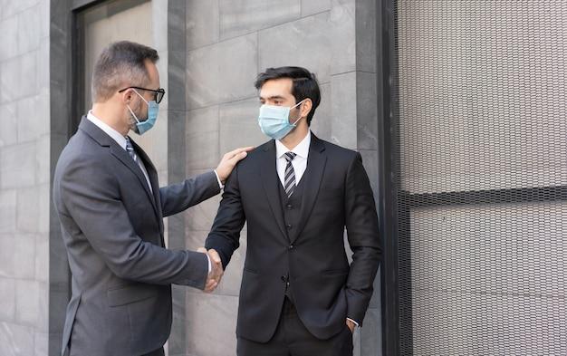 Dwóch biznesmenów rasy kaukaskiej nosi maski medyczne witając się uściskiem dłoni na ulicy w mieście