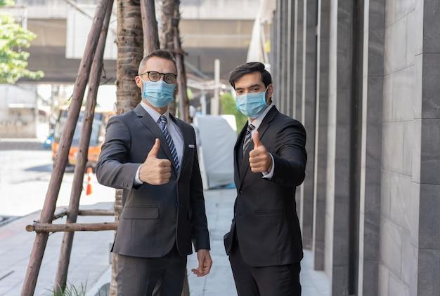 Dwóch biznesmenów rasy kaukaskiej w masce medycznej pokazującej kciuki do góry podczas epidemii koronawirusa covid-19 na ulicy