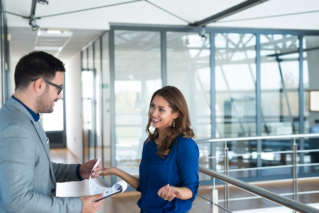 Dwóch biznesmenów rozmawia na korytarzu firmy.
