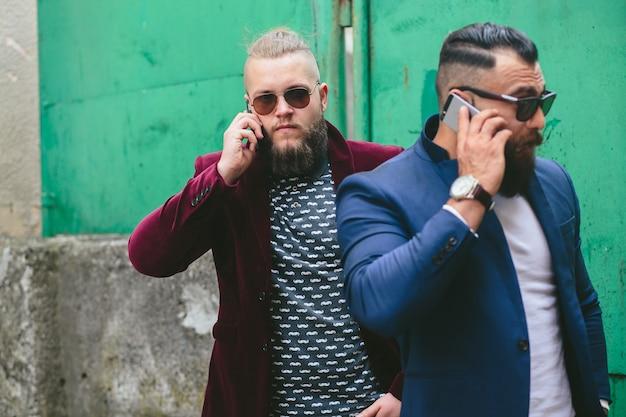 Dwóch biznesmenów rozmawiających przez telefon w mieście