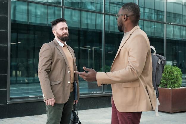 Dwóch biznesmenów rozmawiających ze sobą, stojąc w pobliżu budynku biurowego na zewnątrz