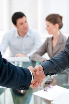 Dwóch biznesmenów, ściskając ręce po zapieczętowaniu umowy podczas spotkania w biurze