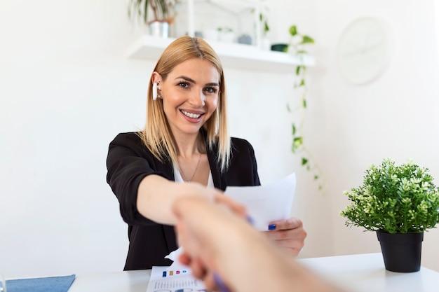 Dwóch biznesmenów ściskających dłonie nad biurkiem, gdy finalizują transakcję lub partnerstwo, skupiają się na uśmiechniętej młodej blond kobiecie
