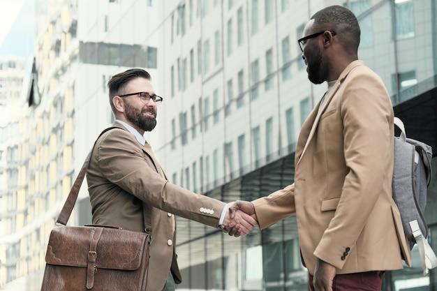 Dwóch biznesmenów, ściskających dłonie, witających się podczas spotkania w mieście