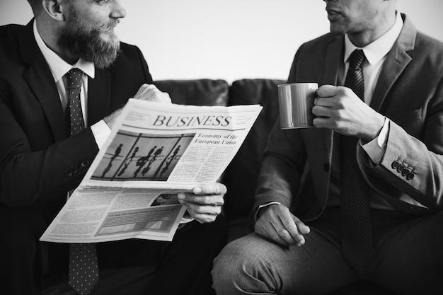 Dwóch biznesmenów siedzi na kanapie