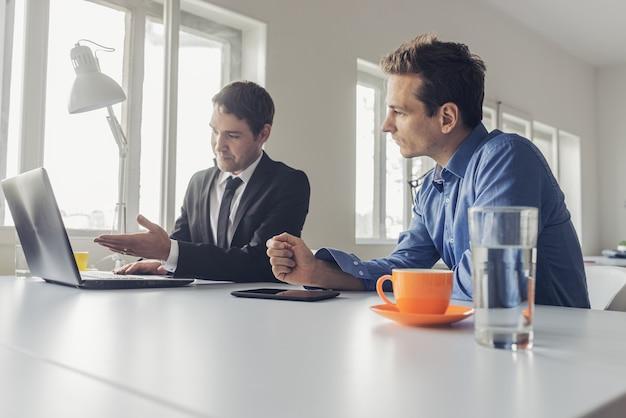 Dwóch biznesmenów siedzi przy biurku, pracując razem nad projektem za pomocą laptopa i cyfrowego tabletu.