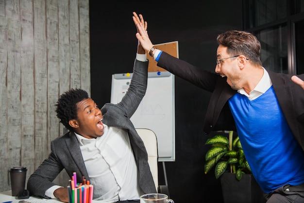 Dwóch biznesmenów świętuje zwycięstwo, osiągnięcie celu, przybicie piątki
