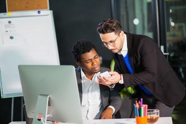 Dwóch biznesmenów szuka inteligentnego telefonu