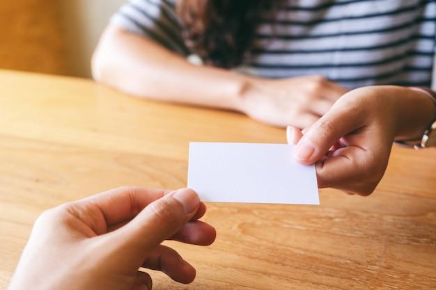 Dwóch biznesmenów trzymających i wymieniających pustą wizytówkę