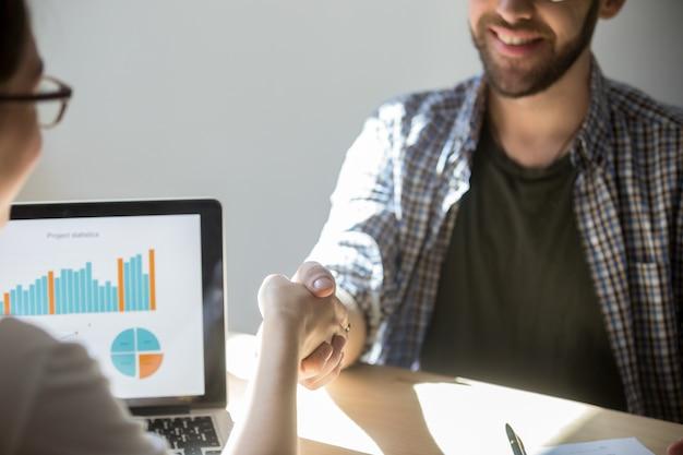 Dwóch biznesmenów uścisnąć dłoń, aby zapieczętować umowę z uśmiechem.