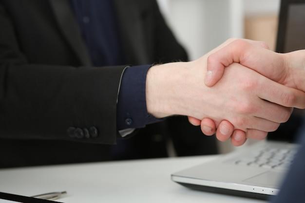 Dwóch biznesmenów uścisnąć dłoń jako cześć w biurze zbliżenie