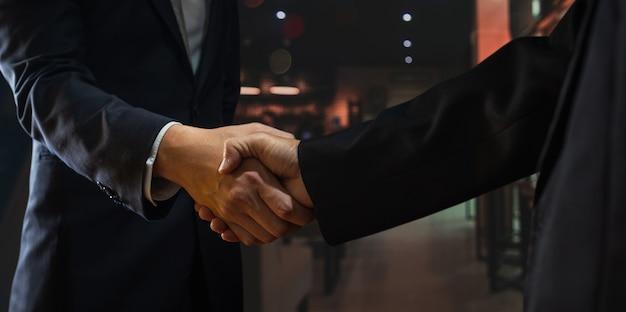 Dwóch biznesmenów uścisnąć dłoń z partnerem