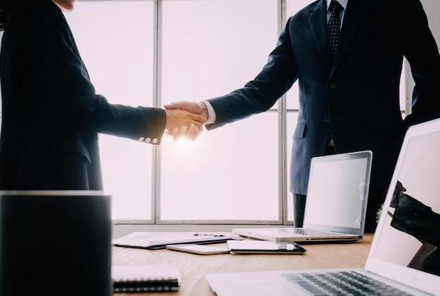 Dwóch biznesmenów uścisnąć dłoń.