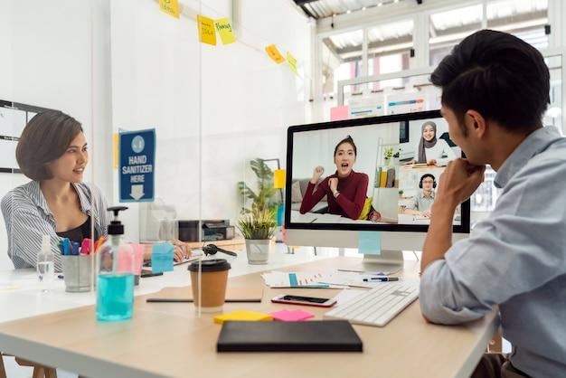 Dwóch biznesmenów z azji pracowało w domowym biurze i uczestniczyło w spotkaniu wideokonferencyjnym