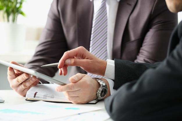 Dwóch biznesmenów z tabletem i wykresami biznesowymi przy biurku