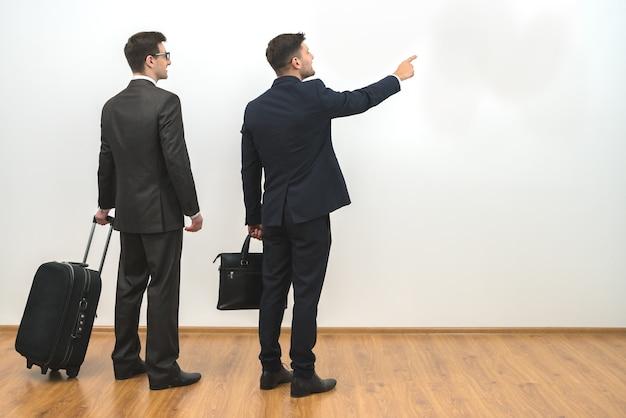 Dwóch biznesmenów z torbami gestykuluje na tle białej ściany