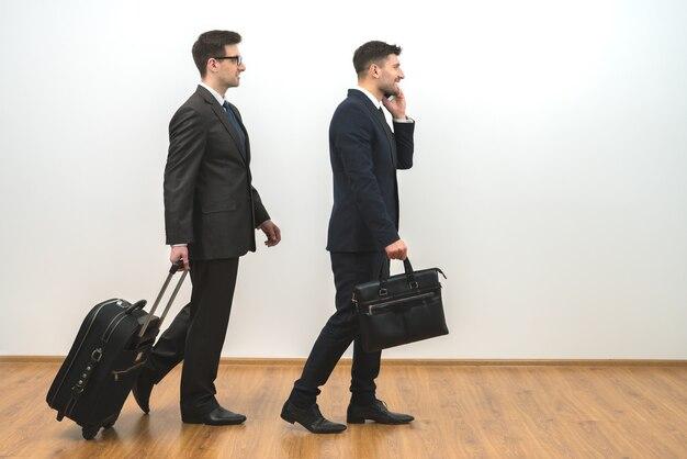 Dwóch biznesmenów z torbami telefonuje na tle białej ściany