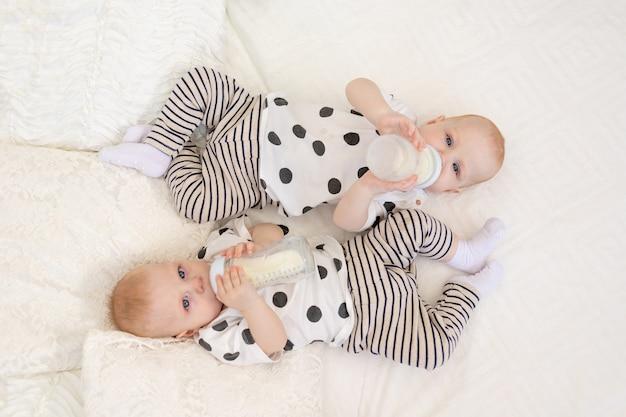 Dwóch bliźniaków, brat i siostra w wieku 8 miesięcy, leżą na łóżku w piżamie i piją mleko z butelki, koncepcja jedzenia dla niemowląt, widok z góry, koncepcja przyjaźni, miejsce na tekst