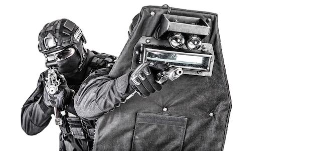 Dwóch bojowników policyjnego zespołu szybkiego reagowania, członkowie swat, strzelcy z firmy ochroniarskiej celujący z pistoletu i karabinu szturmowego, chowając się za osłoną balistyczną, strzelanie studyjne na białym tle
