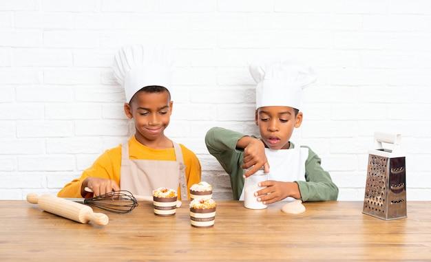 Dwóch braci afroamerykanów ubranych jak szef kuchni