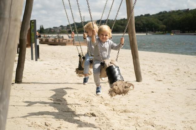 Dwóch braci bliźniaków chłopców chłopców grających na placu zabaw dla dzieci w słoneczny jesienny dzień.