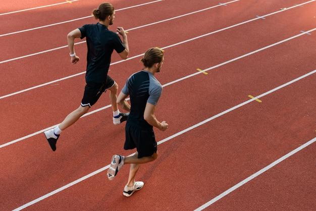 Dwóch braci bliźniaków sportowców biegających na stadionie na świeżym powietrzu.