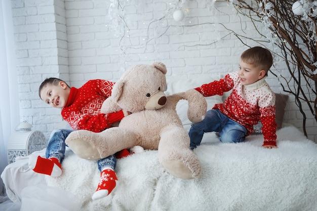 Dwóch braci chłopiec w świątecznym czerwonym swetrze z wizerunkiem jelenia siedzącego na łóżku z poduszkami.