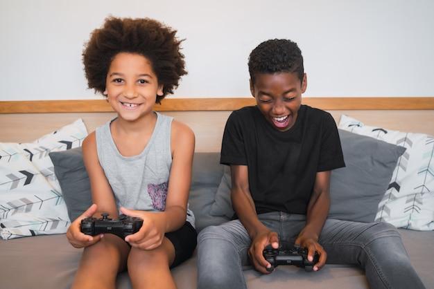 Dwóch braci grających w gry wideo w domu.