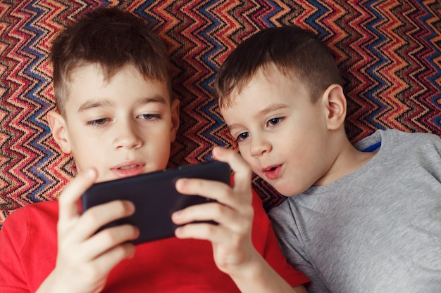Dwóch braci leżących grając w grę w telefonie