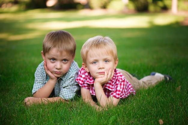 Dwóch braci leżących na trawie w parku na zewnątrz, uśmiechając się i