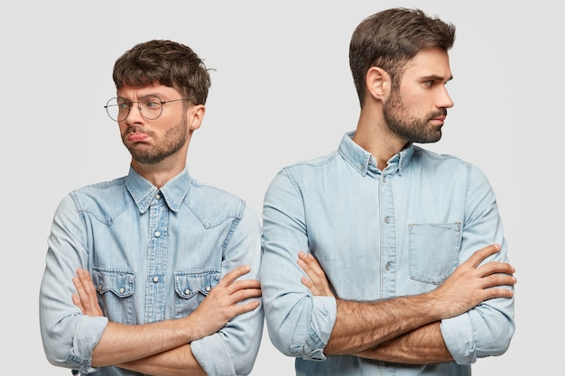 Dwóch braci nie może dzielić domu, ma założone ręce, nie patrzy na siebie, kłóci się