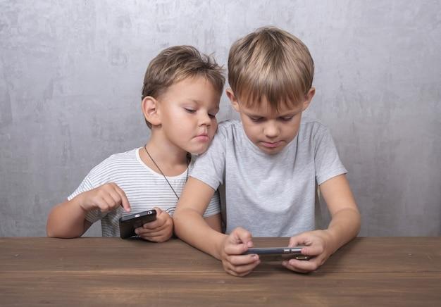 Dwóch braci o europejskim wyglądzie grających w gry na smartfonach, siedzących przy stole w pokoju