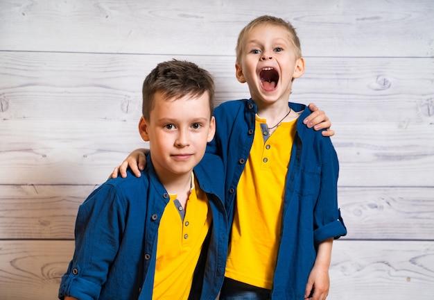Dwóch braci przytulonych, patrząc. chłopcy w tych samych ubraniach pozujących razem. jedno dziecko z otwartymi ustami, a drugie patrząc prosto.