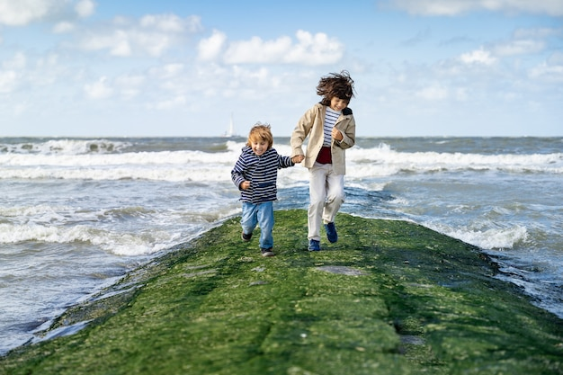 Dwóch braci trzymających się za ręce biegnie po falochronie na morzu północnym. roześmiani chłopcy spędzający weekend nad morzem w belgii, knokke. przyjaźń rodzeństwa.