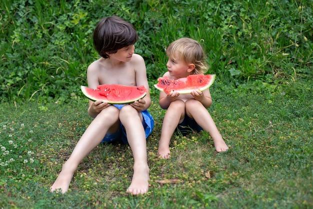 Dwóch braci z dużymi czerwonymi kawałkami arbuza siedzi na zielonej trawie w parku latem lub na placu zabaw. koncepcja pikniku obozu kidnergartnen