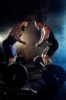Dwóch brodatych, wytatuowanych, muskularnych mężczyzn patrzy na siebie i krzyczy na siłowni.