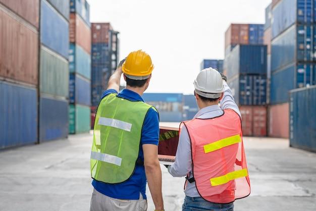 Dwóch brygadzistów z laptopem sprawdzających pozycję załadunku skrzyni ładunkowej ze statku towarowego cargo