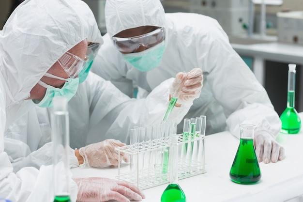 Dwóch chemików eksperymentujących z zieloną cieczą