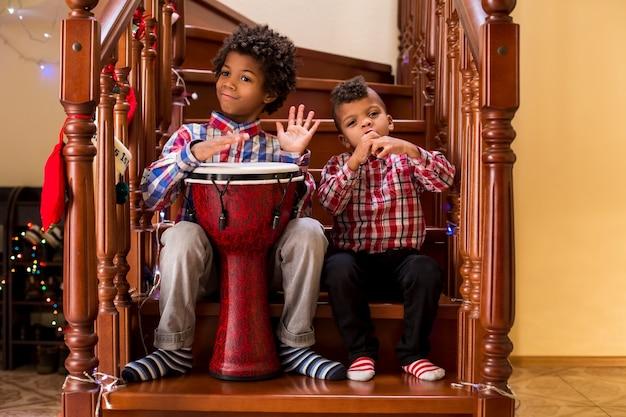 Dwóch chłopców afro gra muzykę dzieciaki grające muzykę na schodach kreatywny duet młodych muzyków rozpoczynających mu...