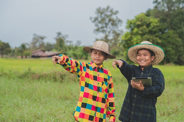 Dwóch chłopców azjatów za pomocą tabletu stojącego rolnika drzwi, koncepcja inteligentny rolnik lub szkoła nauki kolażu edukacji