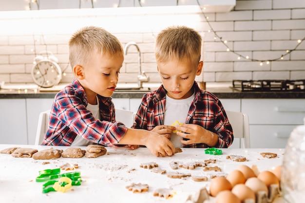 Dwóch chłopców bliźniaków przygotowuje ciasteczka na boże narodzenie lub nowy rok w jasnej kuchni.