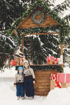 Dwóch chłopców braci na świątecznym targu ze słodyczami na świeżym powietrzu