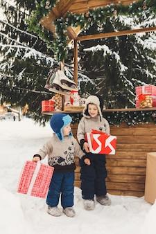 Dwóch chłopców braci z pudełkami na prezenty na świątecznym targu ze słodyczami na świeżym powietrzu