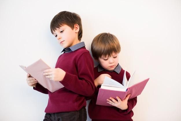 Dwóch chłopców czyta książkę w studio.