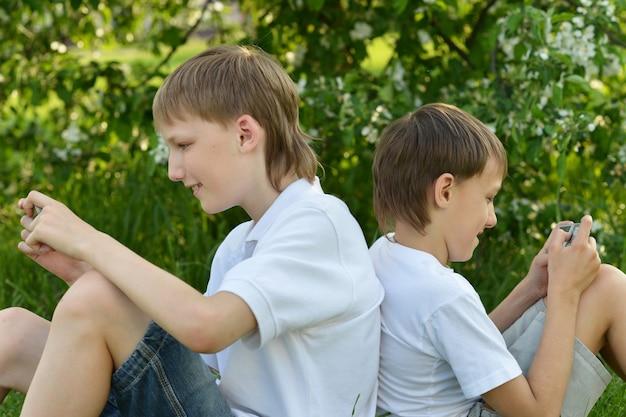 Dwóch chłopców gra przez telefon na dworze