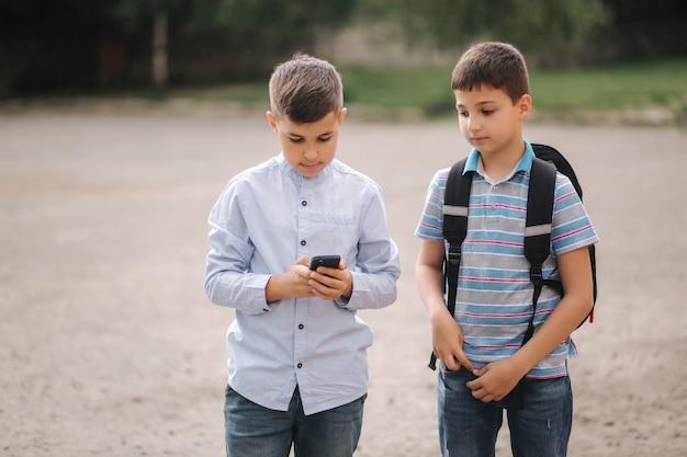 Dwóch chłopców gra w gry online w kwarantannie. młodzi chłopcy uśmiechają się i używają telefonu. jedno spojrzenie, jak grać innym