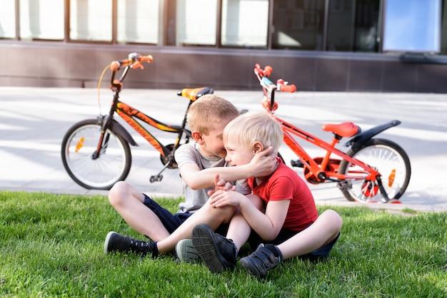 Dwóch chłopców komunikuje się siedząc na trawie. odpoczywaj po rowerze, rowery
