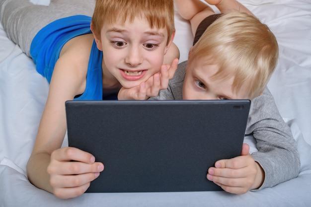 Dwóch chłopców leży w łóżku i patrzy na tablet. gadżety rekreacyjne