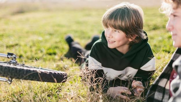 Dwóch chłopców odpoczywa na trawie podczas jazdy na rowerach